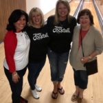 4 women pose together at a bowling alley